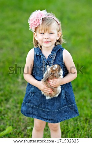 portrait of little girl outdoors with bunny - stock photo