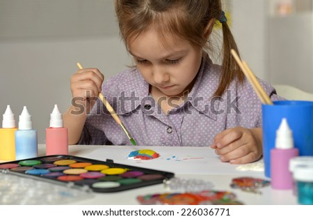 Portrait of little girl painting at home