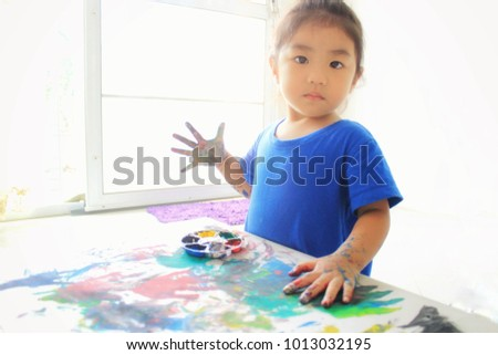 Portrait of little girl painting at home,Little asian girl sitting at table in room and painting on paper,education and children activities concept
