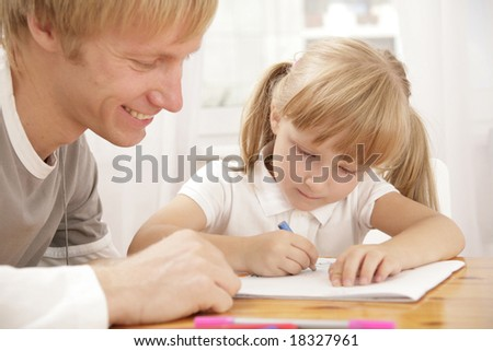 Portrait of little girl painting something and her father looking at this - stock photo