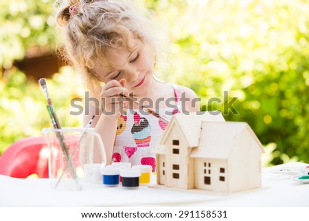Portrait of little girl paints wooden model of house,  summer outdoor, new home concept - stock photo