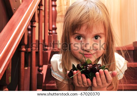 Portrait of little girl playing in home on stairs with plastic cherry berry - stock photo