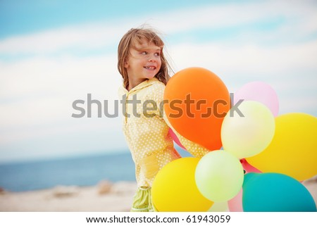 Portrait of little girl playing with air balloons at the beach - stock photo