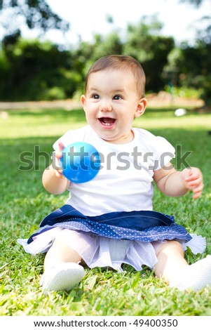 portrait of little girl playing with ball outdoors - stock photo
