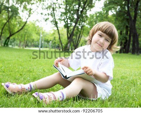 Portrait of little girl reading a book in the summer park - stock photo