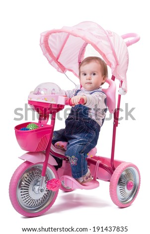 Portrait of little girl riding a children trike. Isolated on white background - stock photo