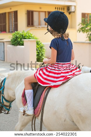 Portrait of little girl riding pony. From the back. - stock photo