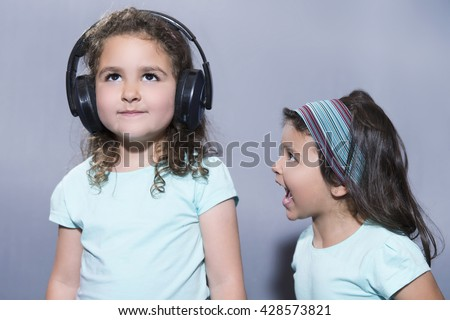 Portrait of little girl screaming at her older sister listening to music in headphones - stock photo
