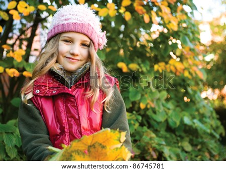 Portrait of little girl showing the yellow autumn leafs