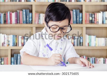 Portrait of little girl sitting in the library while drawing on a paper with a marker and wearing glasses