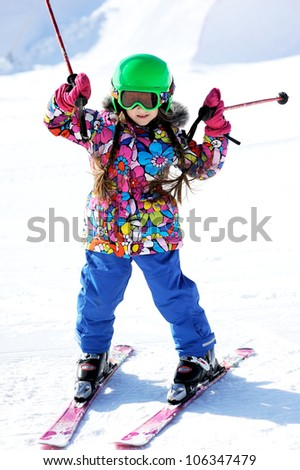 Portrait of little girl skier in sports suit finishing the ride - stock photo