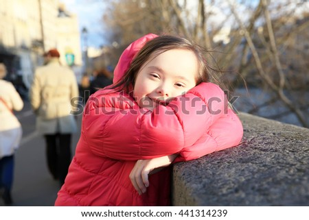 Portrait of little girl smiling in the city - stock photo