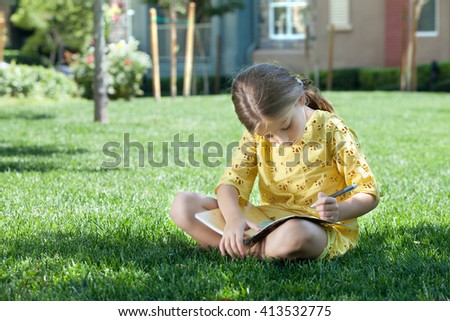 portrait of little girl studying on the grass in summer environment - stock photo