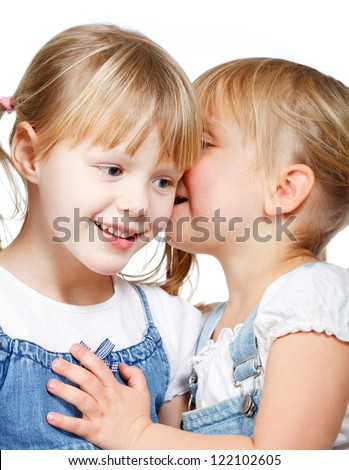 Portrait of little girl  telling a secret to her friend over a white background - stock photo