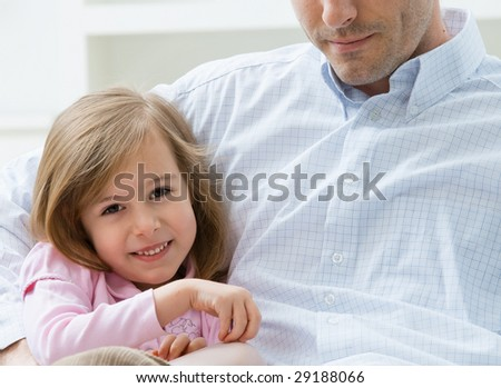 Portrait of little girl wearing pink dress sitting on couch embraced by her father, smiling.