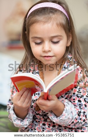 Portrait of little girl with a book - stock photo