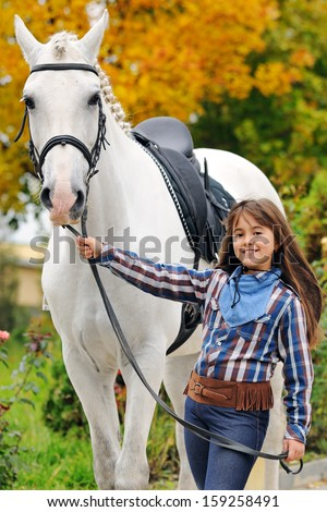 Portrait of little girl with big white horse in autumn - stock photo