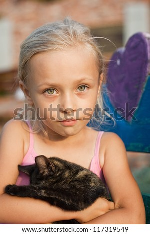 Portrait of little girl with cat - stock photo