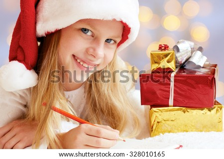 Portrait of little girl with Christmas gifts on the colored background. Christmas dreams. - stock photo