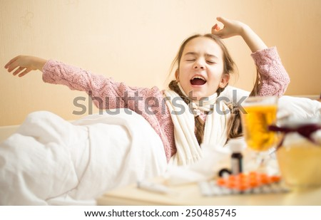 Portrait of little girl with flu yawning in bed at morning - stock photo