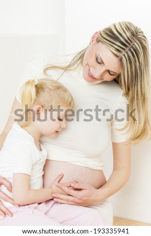 portrait of little girl with her pregnant mother
