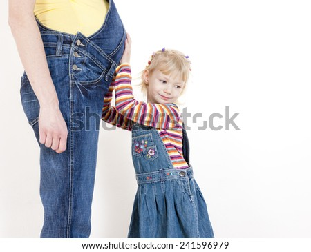 portrait of little girl with her pregnant mother - stock photo