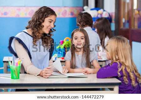 Portrait of little girl with kindergarten teacher and friend sitting at desk in classroom - stock photo