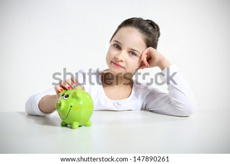 Portrait of little girl with piggy bank isolated on white - stock photo