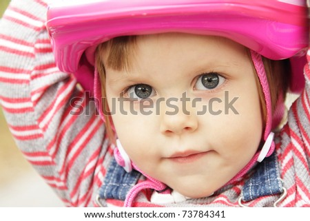 Portrait of little girl with pink bicycle helmet - stock photo