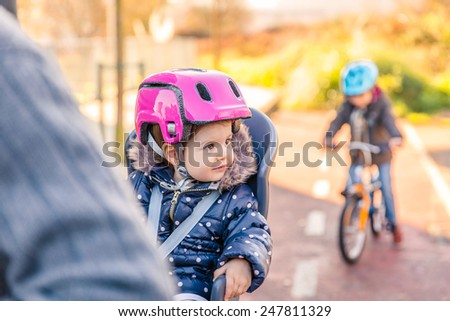 Portrait of little girl with security helmet on the head sitting in bike seat and her brother with bicycle on the background. Safe and child protection concept - stock photo