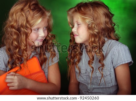 Portrait of little girls looking each other - stock photo