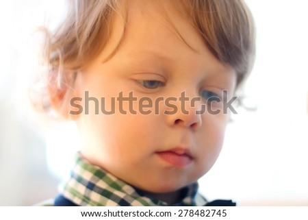 Portrait of little handsome serious boy with curly hair. Close up view - stock photo