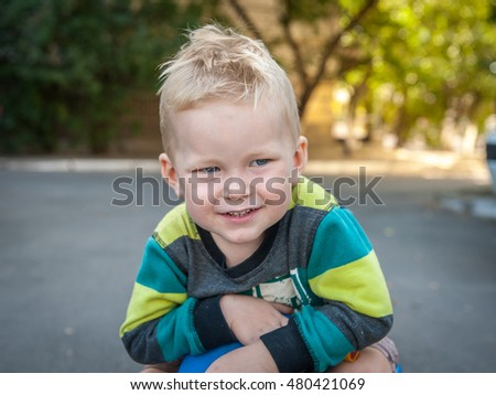 portrait of little happy boy in toy car. background summer park. Funny boy car driver