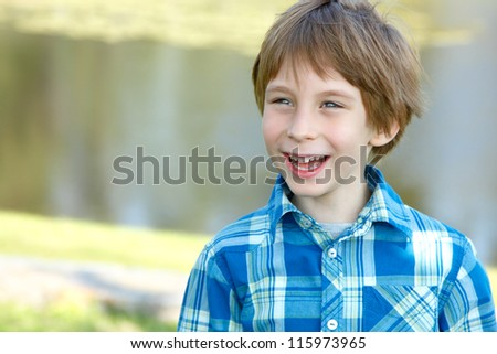 portrait of little happy boy over sunny nature background, laughing child in summer park outdoor