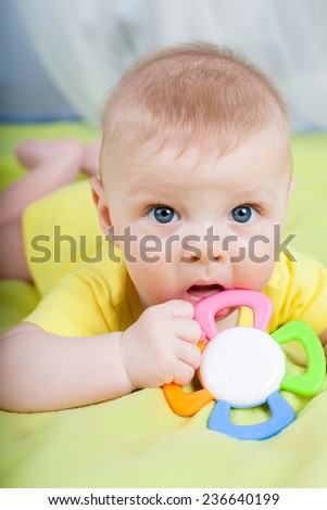 portrait of little kid  lying on his stomach with teether in the hands