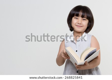 Portrait of little lovely Asian child reading a book - stock photo
