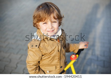 Portrait of little preschool boy having fun and riding his bike  in the city - stock photo