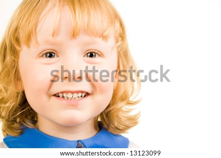 Portrait of little redhead girl happily smiling and looking at camera - stock photo