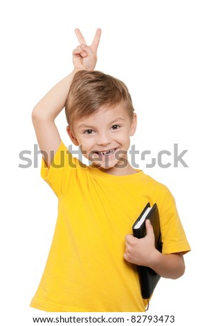 Portrait of little schoolboy holding book on white background - stock photo