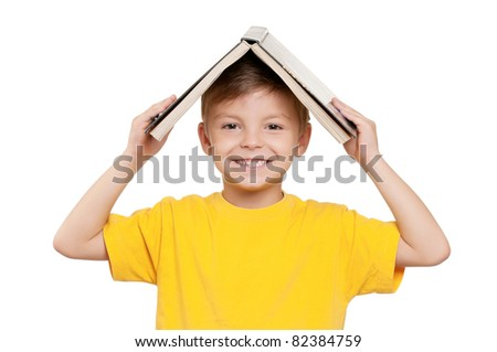 Portrait of little schoolboy with book on white background - stock photo