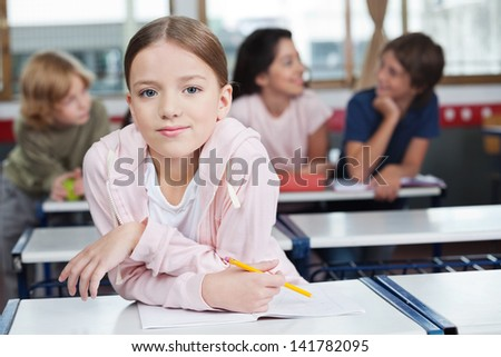Portrait of little schoolgirl leaning on desk with students in background - stock photo
