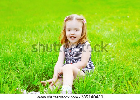 Portrait of little smiling girl child on the grass in sunny summer day