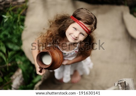 portrait of little smiling girl with jar with milk - stock photo
