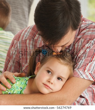 Portrait of little tired daughter resting, father kissig top of head. - stock photo