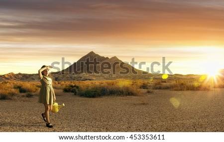 Portrait of little white girl walking through the desert during sunset - stock photo