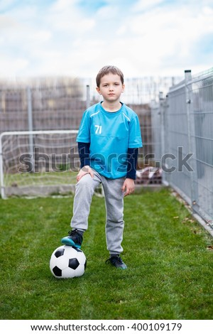 Portrait of little 7 years boy - footballer with his feet on football ball. Child playing football in garden. Wears a blue t-shirt, black and blue shoes and grey sweatpants.  - stock photo
