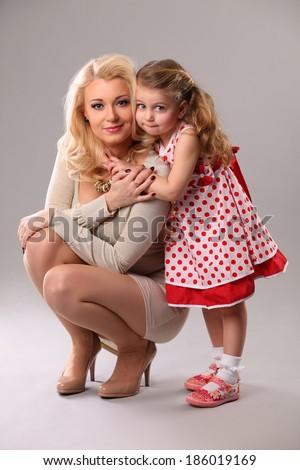 portrait of little 3 years old girl hugging her mom in studio  - stock photo