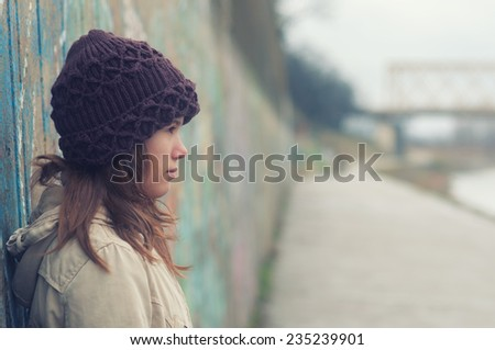 Portrait of lonely teenage girl on moody winter day. - stock photo