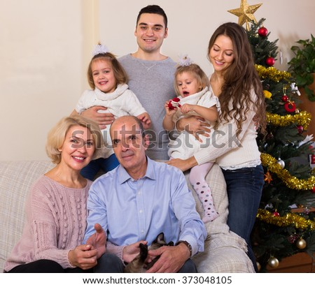 portrait of long family with grand children decorating New Year tree - stock photo