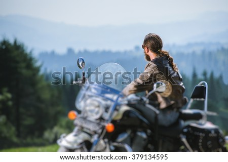 Portrait of long-haired guy in sunglasses jeans and a leather jacket sitting on a black custom motorcycle and looking into distance. Sunny day in the mountains. View from the back. Tilt blur effect - stock photo